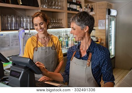 Two happy coffeehouse waitresses in apron smiling and working on cash register. Mature and smiling women working behind the counter of coffee shop. Two happy waitresses working at cafeteria.