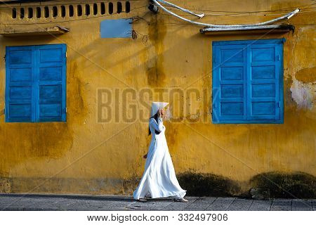 Young Vietnamese Woman In White Tunic  Walking In Front Of A Weathered Gold Stucco Wall With Blue Sh