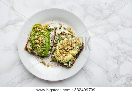 Healthy Avocado Toasts For Breakfast Or Lunch With Rye Bread, Sliced Avocado, Arugula, Pumpkin And S
