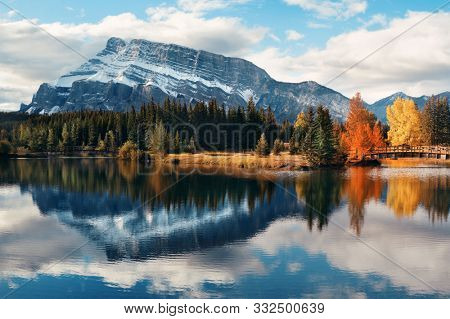 Two Jack lake with snow mountain Autumn foliage and water reflection in Banff National Park in Canada.