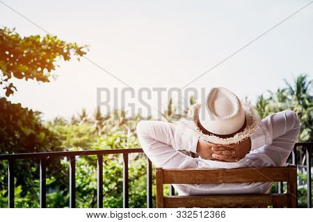 Back Side Of Senior Asian Woman Relaxing Or Enjoying Travel Vacation Travel On Wooden Chair At Balco