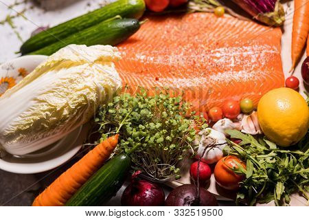 Closeup Food Photo Of Vegetables, Herbs And Salmon Fish On The Table. Chinese Cabbage, Lemon, Tomato