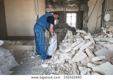 Worker Removes Debris From The Destroyed Wall