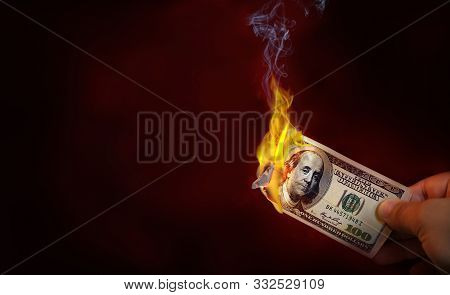 Hand Holding A Burning 100 Dollar Bill Money With Copy Space.