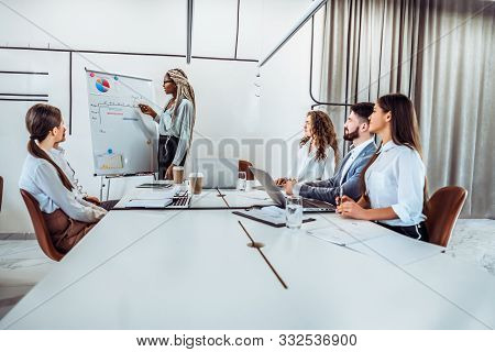 Concentration At Work.a Young Business Woman Tells Her Colleagues A Work Plan For The Week. Business