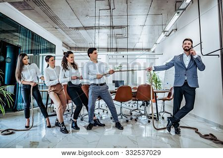 Conceptual Business. A Happy Boss Calmly Talks On The Phone While His Employees Work. Tug Of War - E