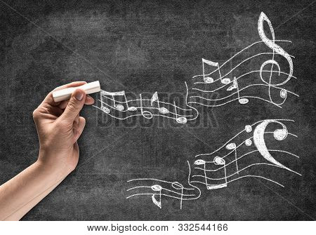 Businessman Hand With Chalk Draws Music Notes Sketch On Chalkboard. Freehand White Chalk Illustratio