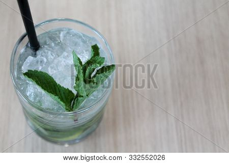 Glass Of Mojito Cocktail On Wooden Table With Black Straw, Ice And Mint Leaf. Copy Space For Text. A