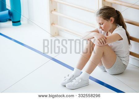 Demotivated girl sitting alone in a gym hall during classes poster