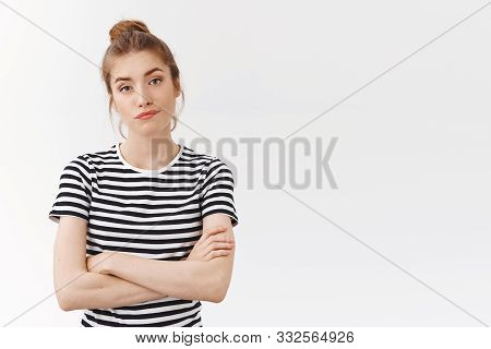 Skeptical Sassy Young Woman In Striped T-shirt With Messy Bun, Cross Hands Chest And Smirk, Pouting