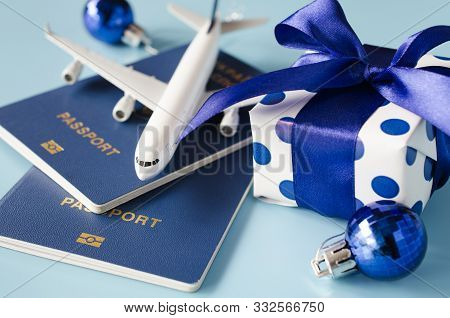Christmas Or New Year Travel Concept. Toy Airplane With Passports And Gift Box On Blue Background.