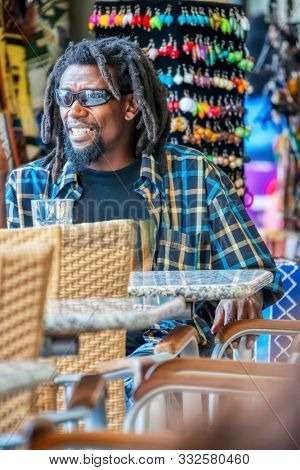 Young rasta man resting at a table in a coffeeshop, african art in the background