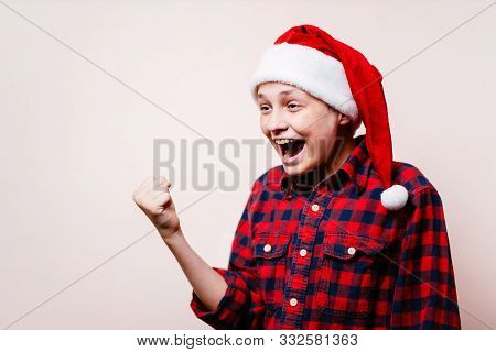Victory, Success, Achievement. Excited Thrilled Agitated Boy In Christmas Hat Making Win Gesture, Ad