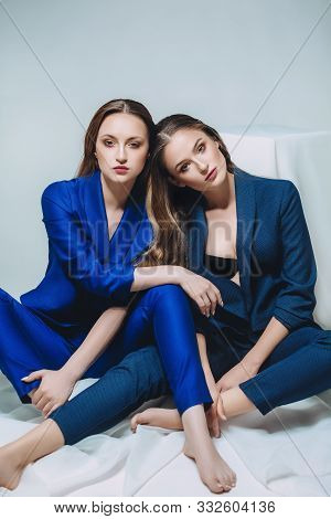 Beautiful Portrait Of Two Sisters  In A Fashionable Way. Stock Photo