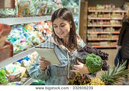 A Young Woman With A Notebook Buys Groceries In The Supermarket.