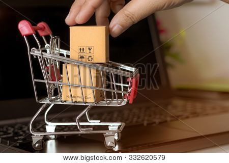 Hand Holding Cardboard Box With Symbols In Trolley On Laptop Keyboard. Consumer Can Buy Products Dir
