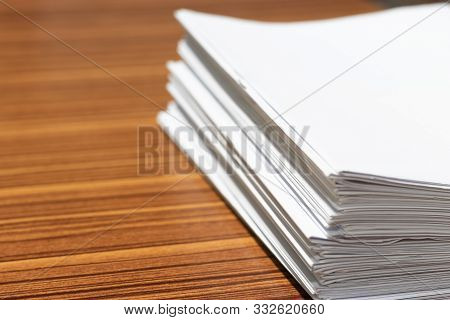 Stack Of Homework Assignment On Office Wooden Desk Waiting To Be Managed And Inspected For Score. Pi