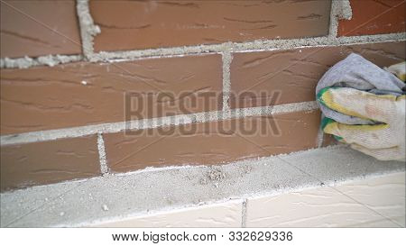 Worker Wipes The Seams In The Brickwork. Worker Rewrites A Brick Wall. Brick House Construction