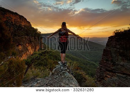 Adventurous Hiiker Standing Firm On The Narrow Cliff Ledge Of The Mountain Gully Looking Out To Dist