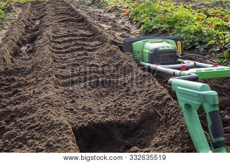 Power cultivator or tiller machine handle in close-up with a just ploughed furrow in background poster