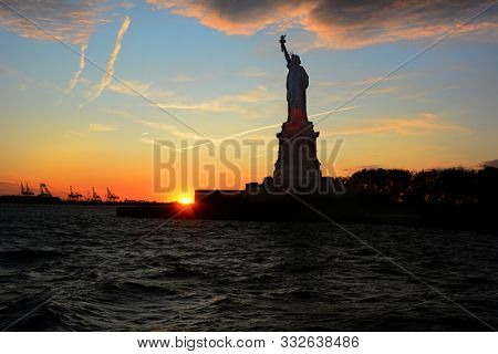 Statue of Liberty in silhouette at sunset viewed from the water with clouds and colorful sky.