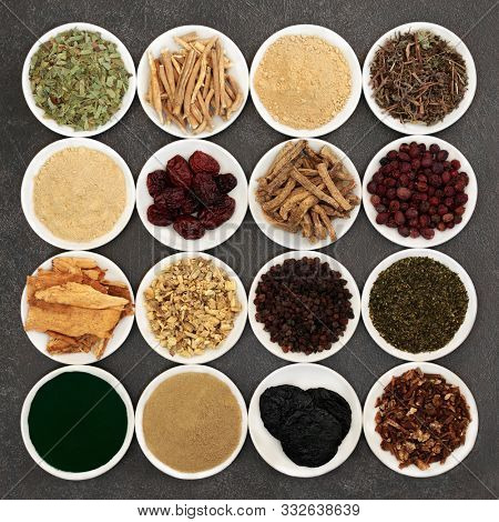 Herbs for vitality, energy & fitness used in natural alternative & Chinese herbal medicine. In porcelain bowls on grey grunge background. Health care concept. Flat lay.