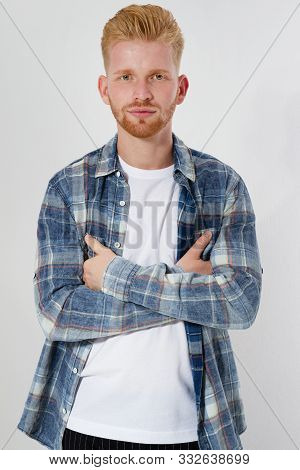 Casual Young Red-head Man Looking At Camera With Arms Crossed And Satisfaction Isolated