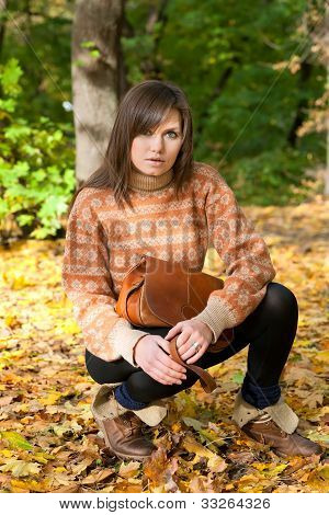Young Girl With Handbag Sitting In The Forest