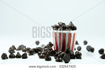 Many Chocolate Chips Are On Gray Abstract Background. Background With Chocolate. Slices Of Chocolate