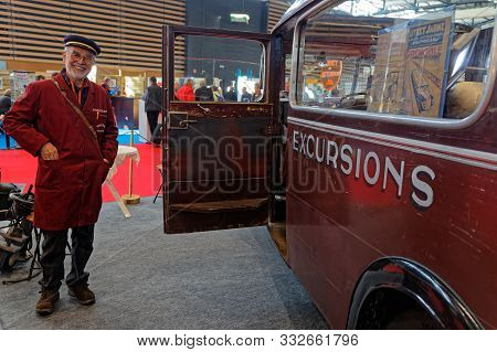 Lyon, France, November 8, 2019 : Old Bus And Driver At The Motorshow. The Salon Epoq Auto Stands In