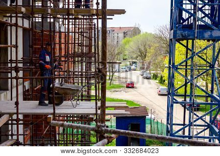 Scaffold With Wooden Platform Is Placed Against Edifice, Building Under Construction.