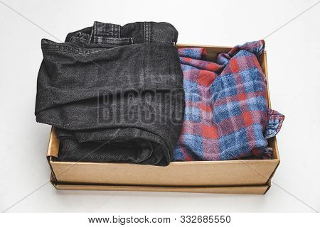 Clothes In A Card Box On A White Background. Charity Help For People In Need - Box With Donation Clo