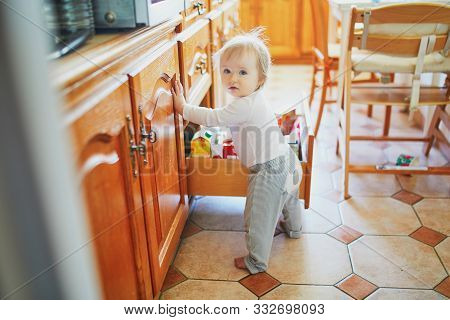 Adorable Toddler Girl At Home, Opening The Drawer In The Kitchen And Selecting Food. Curious Little