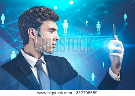 Young Handsome European Businessman Using Smartphone With Facial Recognition Technology Over Blue Ba