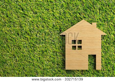 Little Wooden Miniature House Model On Green Grass Background With Copy Space - Ecological Living Or