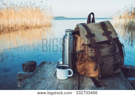 Enameled Mug Of Coffee Or Tea, Backpack Of Traveller And Thermos On Wooden Pier On Tranquil Lake.