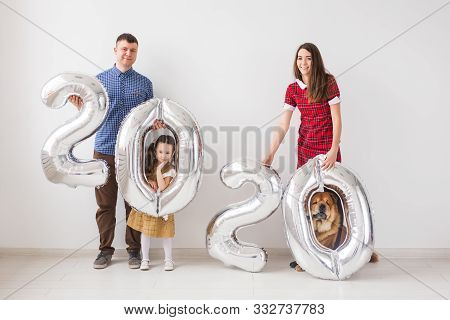 New 2020 Year Is Coming Concept - Happy Family With Dog Are Holding Silver Colored Numbers Indoors.