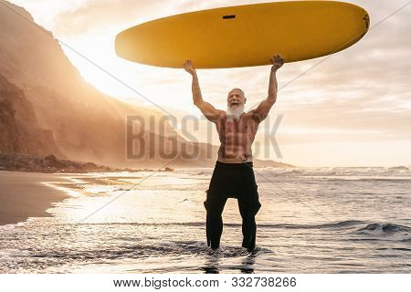 Happy Fit Senior Having Fun Surfing At Sunset Time - Sporty Bearded Man Training With Surfboard On T