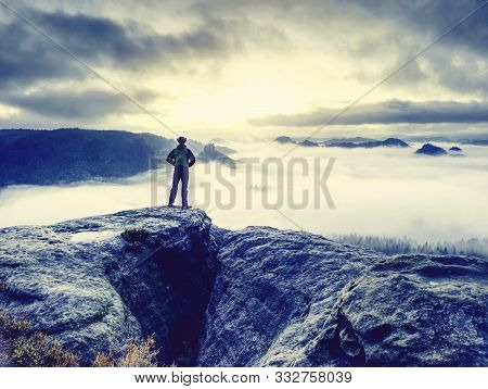 Lone Male Hiker Looks Out Over High Mountains And Valley. Storm Heavy Clouds Gather Over The High Pe