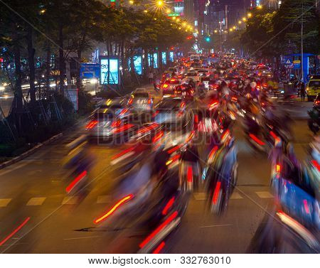 Blurred Cars And Motorbikes Lights From Traffic Jam At Night Time In Hanoi, Vietnam.