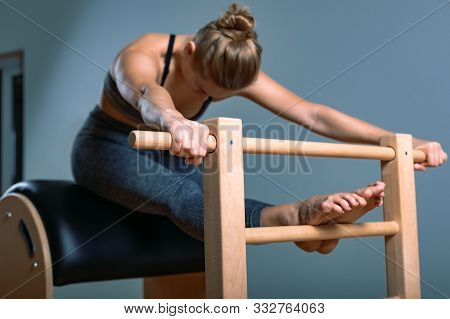 Beautiful Positive Blond Woman Is Being Prepared Performing Pilates Exercise, Training On Barrel Equ