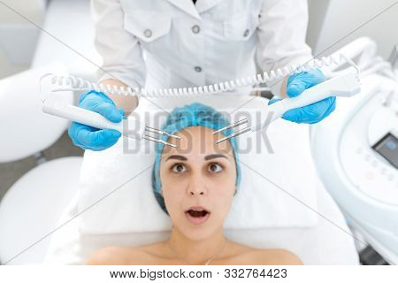 Portrait of a young beautiful girl face microcurrent therapy procedure. Facial care and rejuvenation. Increase epidermal tone. poster