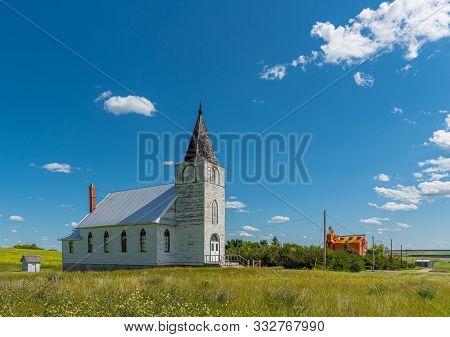 Immanuel Lutheran Church With Grain Elevator In The Background In Admiral, Saskatchewan, Canada