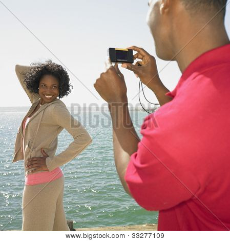 African man talking photograph of African woman next to water