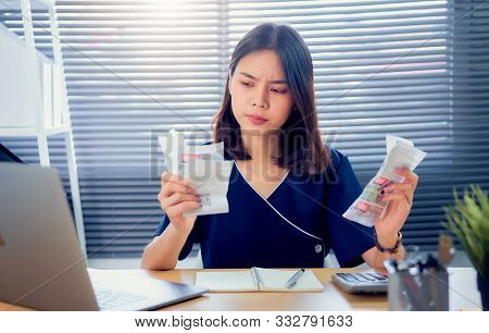 Sad Asian Woman Hand Holding Expense Bill And Calculation About Debt Bills Monthly At The Table In H