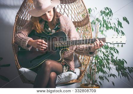 Beautiful Woman Playing Guitar In Swing Chair. Woman Relaxing In Swing Chair At Home. Hipster Lifest