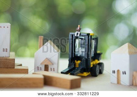 Miniature Banker With Yellow Forklift. Concept Of Risks, Lost Property, Seized, Mortgage