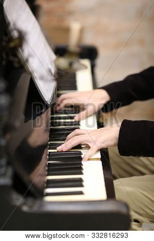 Young Pianist Hands With Piano Keys And Sheet Music Close Up Photo