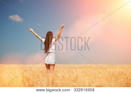 Happy woman enjoying the life in the field Nature beauty, blue sky, bright sun and field with golden wheat. Outdoor lifestyle. Freedom concept. Woman jump in summer field