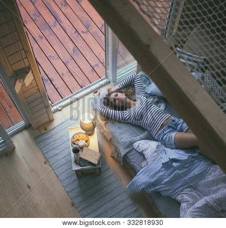 Young woman wearing shorts lying down in bed by the window in a cozy wooden cabin